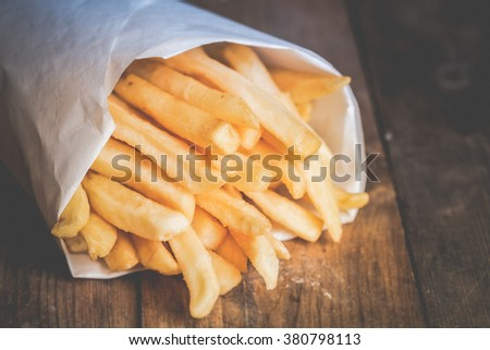 Toned photo. Color tone tuned. French fries on wooden background
