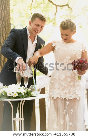 Toned photo of beautiful bride and groom strewing sand in glasses at wedding ceremony - stock photo