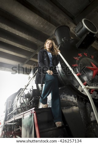 Toned photo of beautiful young woman posing on big black steam locomotive - stock photo