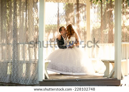 Toned photo of bride sitting on grooms legs on bench at gazebo - stock photo