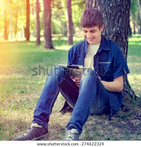 Toned Photo of Cheerful Teenager with Tablet Computer in the Summer Park - stock photo