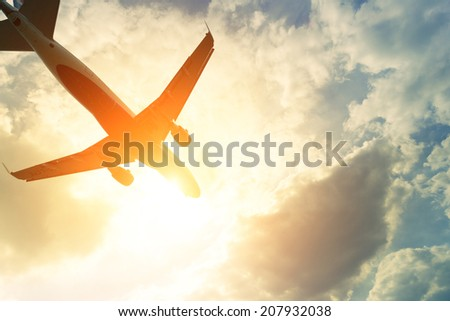 Toned photo of commercial airplane in the sun - stock photo