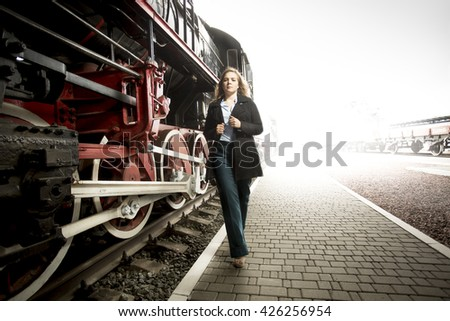 Toned photo of elegant young woman walking on railroad platform past old steam trains - stock photo