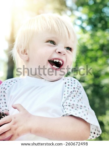 Toned Photo of Happy Baby Boy laugh in the Summer Park - stock photo