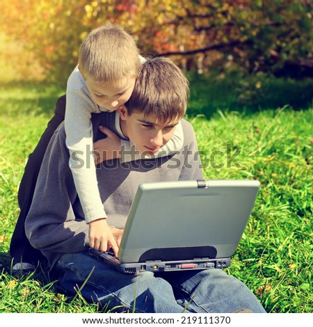 Toned photo of Happy Brothers with Laptop outdoor