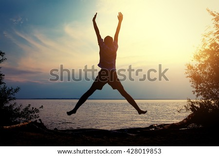 Toned Photo of Happy Person jumping on the Sunset Background