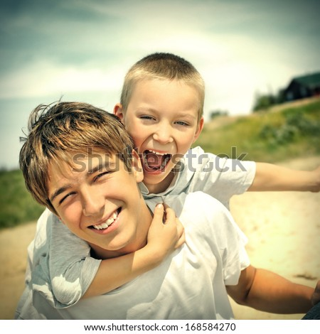 Toned photo of Happy Teenager and Kid Outdoor - stock photo