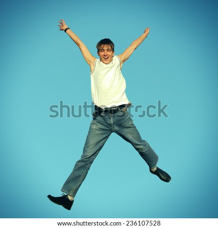 Toned Photo of Happy teenager jumping on the blue sky background - stock photo