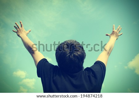 Toned photo of Happy Teenager with Hands Up on the Sky background - stock photo