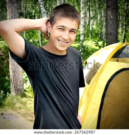 Toned Photo of Happy Young Man camping in the Forest