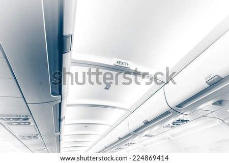Toned photo of long ceiling in airplane with exit sign - stock photo