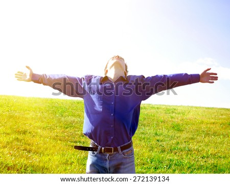 Toned Photo of man rising up his hands in the field