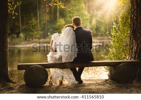 Toned photo of newly married couple sitting on bench at looking at sunset - stock photo
