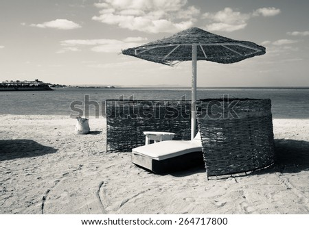 Toned photo of resort beach in retro style, sepia colors. Vintage image - seascape with shoreline and beach umbrella. - stock photo