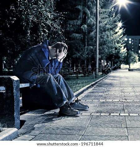 Toned photo of Sad and Lonely Teenager sitting in the Night Park - stock photo