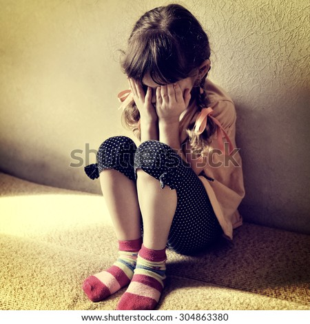 Toned Photo of Sad Little Girl on the Sofa in the Room - stock photo
