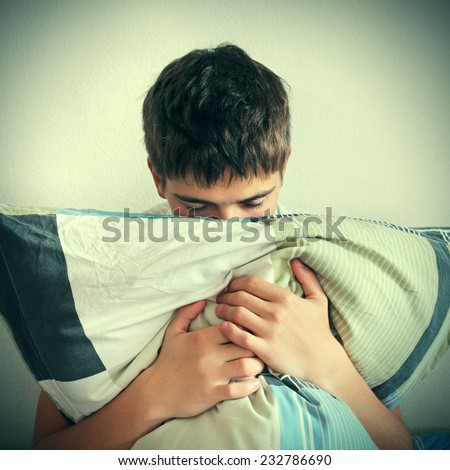 Toned Photo of Sad Teenage with pillow on the Bed at the Home - stock photo