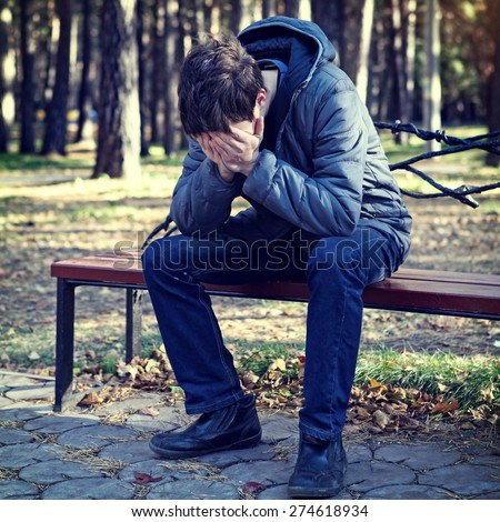 Toned Photo of Sad Young Man in the Autumn Park - stock photo
