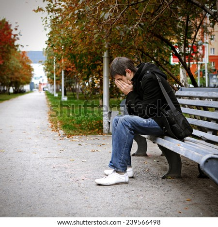 Toned Photo of Sad Young Man sit on the Bench outdoor