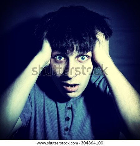 Toned Photo of Scared Young Man on the Dark Background