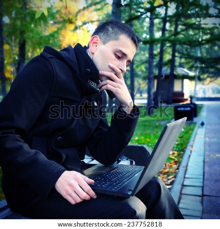 Toned Photo of Serious Young Man with Laptop on the bench in the Park