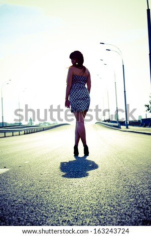 Toned photo of sexy slim woman walking on empty highway - stock photo