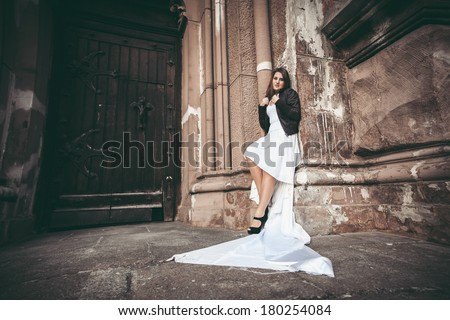 Toned photo of sexy woman in long white dress leaning against ancient wall of abbey - stock photo