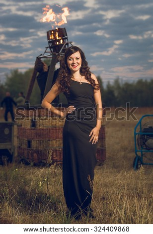 Toned photo of sexy young woman posing next to burning balloon heater - stock photo