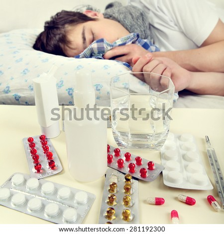 Toned Photo of Sick Young Man on the Bed. Focus on the Pills - stock photo