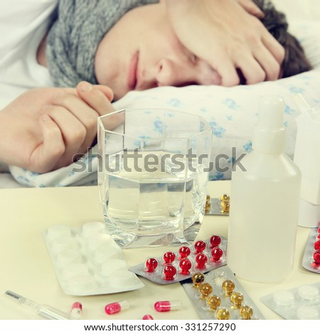 Toned Photo of Sick Young Man sleep on the Bed. Focus on the Pills - stock photo