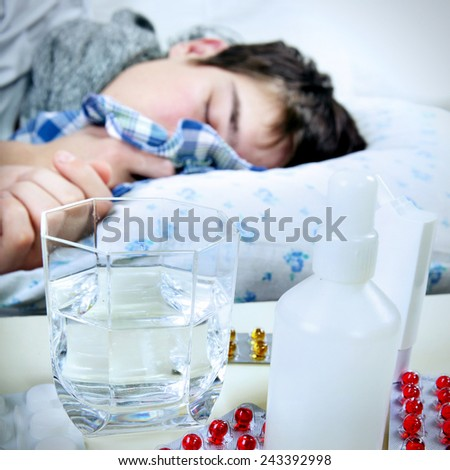 Toned Photo of Sick Young Man sleeps with Pills on foreground Focus on the Pills - stock photo