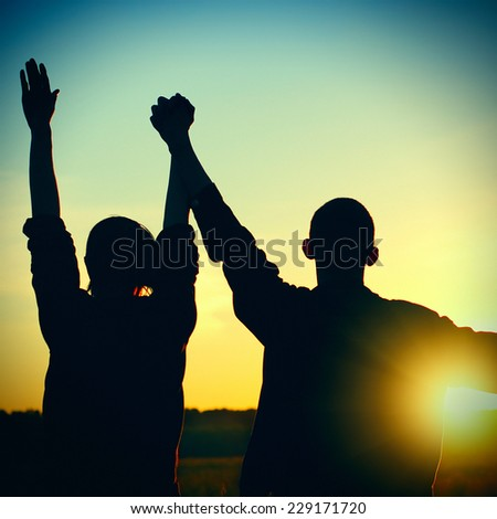 Toned Photo of Silhouette of a Two Friends on Sunset - stock photo