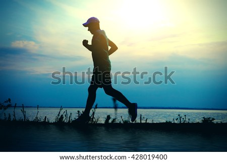 Toned Photo of Silhouette of the Man running on the Sunset Background - stock photo
