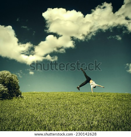 Toned photo of Somersault of Teenage Boy in the Summer Field - stock photo