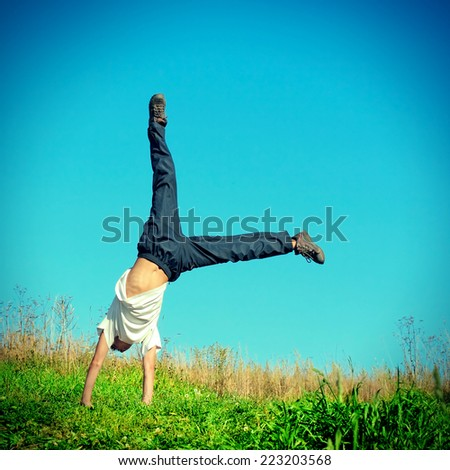 Toned photo of Somersault on Grass of Teenage Boy - stock photo