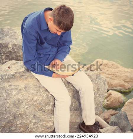 Toned photo of Teenager reading a Book near the Water