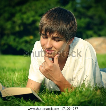 Toned photo of Teenager reads the book on a Summer Lawn