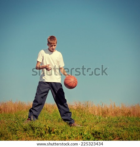 Toned Photo of Teenager with a Ball playing in the Summer Field - stock photo