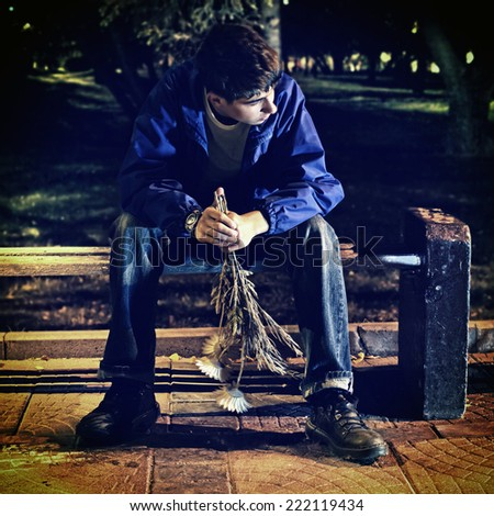 Toned photo of Teenager with Flowers sitting in the Night Park - stock photo