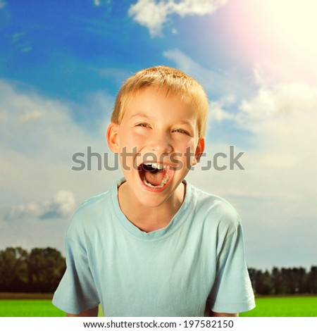 Toned photo of the Happy Kid screaming outdoor - stock photo