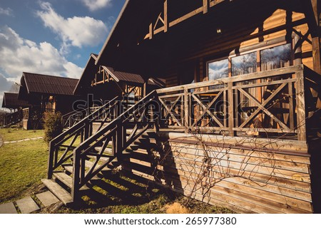 Toned photo of traditional wooden cottage with big terrace - stock photo
