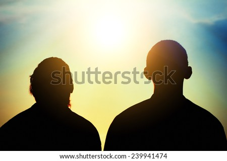 Toned Photo of Two Friends silhouette on evening sky background - stock photo