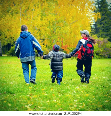 Toned photo of Two Teens and Kid walking in the Autumn Park - stock photo