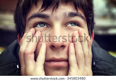 Toned Photo of Unhappy Young Man Portrait outdoor - stock photo