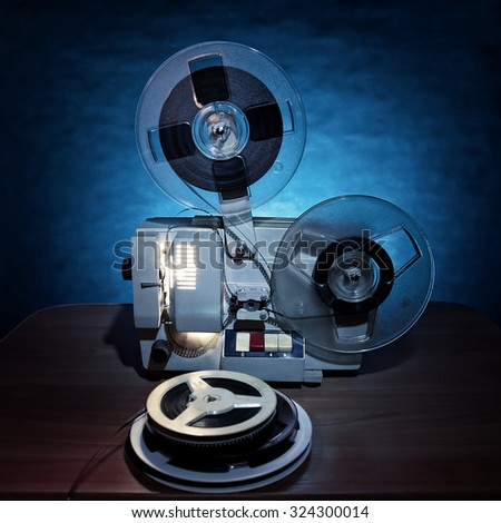 Toned Photo of Vintage Film Projector in the Dusk on the Table - stock photo
