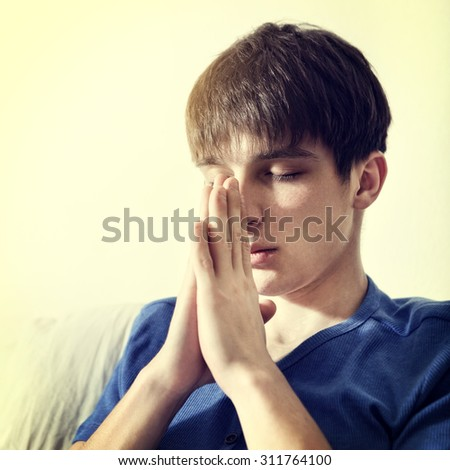 Toned Photo of Young Man Praying at the Home