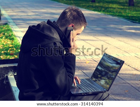 Toned Photo of Young Man with Laptop and Cellphone at the Autumn Park - stock photo