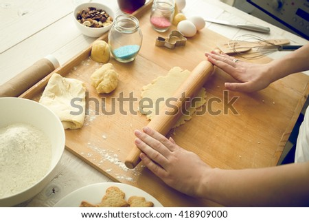 Toned photo of young woman rolling dough on wooden board - stock photo