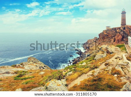 Toned photo with the lighthouse on the rocky coast. Galicia, Spain