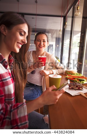 Toned picture of beautiful lady using mobile or smart phone. Best friends or colleagues drinking coffee in cafe or restaurant.